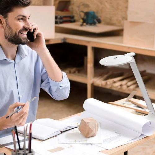 persona usando lámpara halo en escritorio